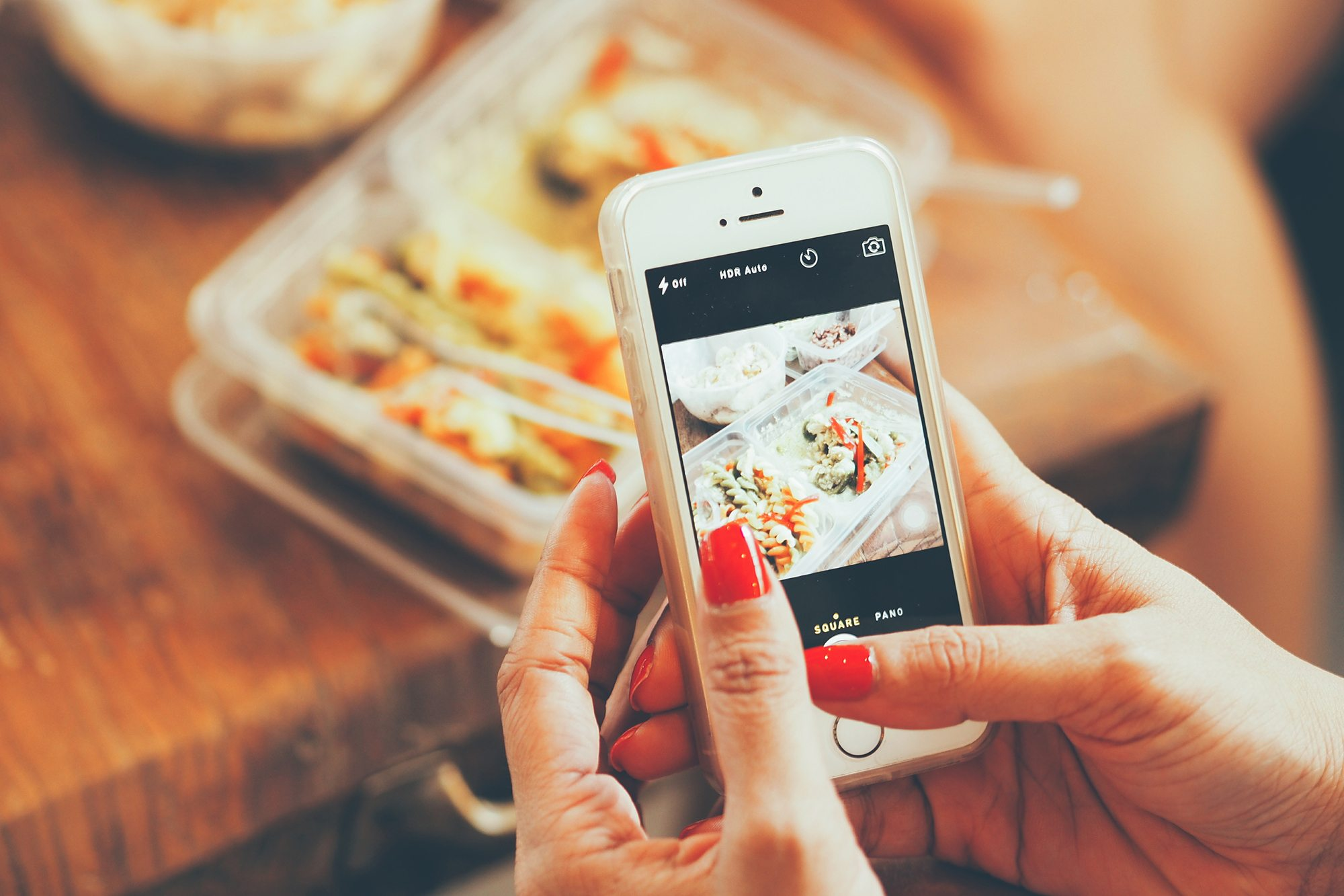 Diner taking picture of food with smartphone