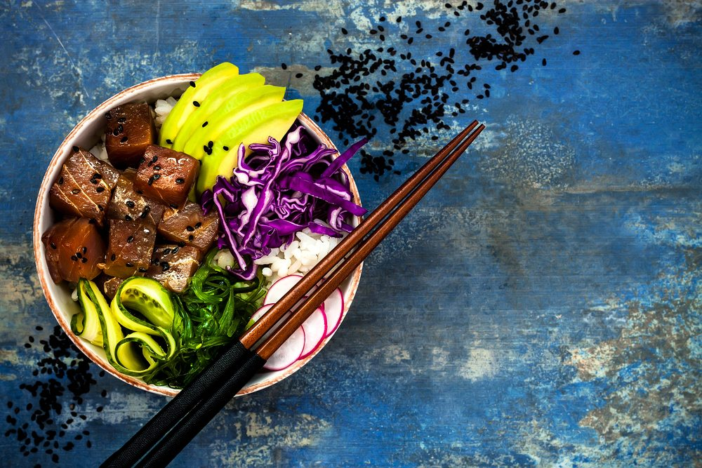 Hawaiian tuna poke bowl with seaweed, avocado, red cabbage, radish, and black sesame seeds