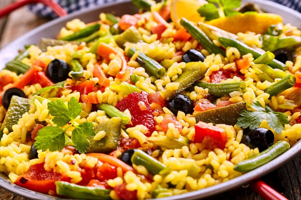 lose-up-of-colorful-and-fresh-vegetarian-paella-spanish-rice-dish-served-in-pan-with-red-handles
